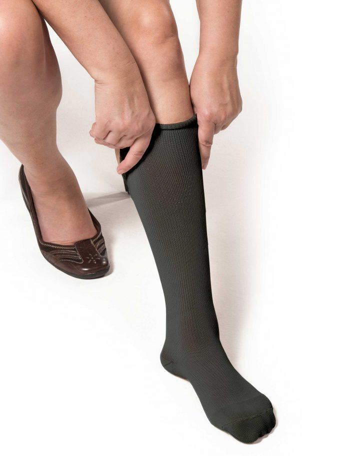 Woman applying gray EXTREMIT-EASE Garment Liner on her left leg