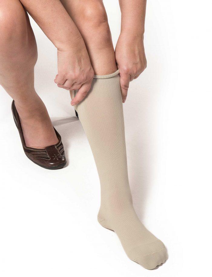 Woman applying tan EXTREMIT-EASE Garment Liner on her left leg