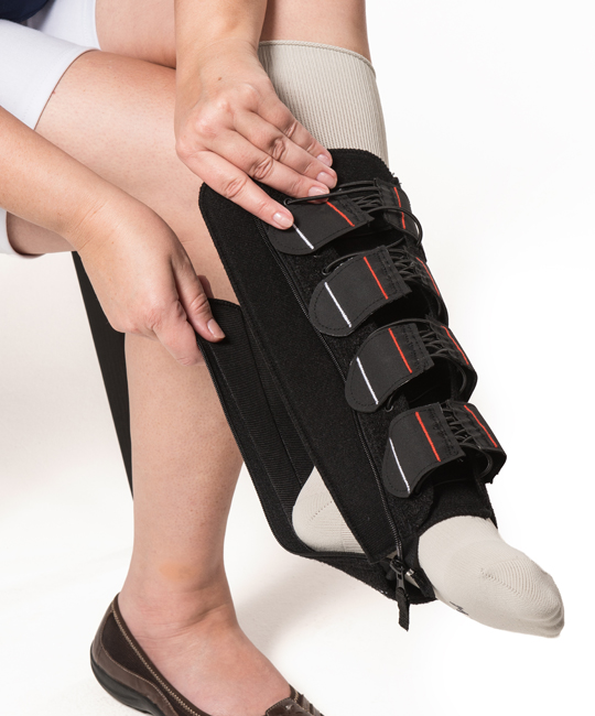 Woman sliding the EXTREMIT-EASE Compression Garment over her foot and on to her leg